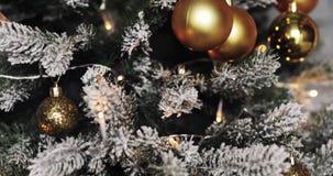 Hälsa säsongbegrepp Docka av prydnader på en julgran med dekorativt ljus och fallande snö stock video