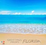 Hälsningar från Florida som är skriftlig på en tropisk strand Royaltyfri Foto