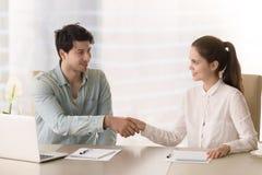 Hälsninghandskakning av affärskvinna- och affärsmansammanträde i b arkivfoton