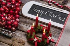 Hälsningkort för glad jul med fyra röda stearinljus och text Royaltyfri Foto