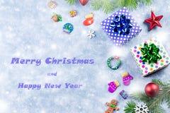 Hälsningkort för glad jul och för lyckligt nytt år med granträdet och garneringar arkivfoton