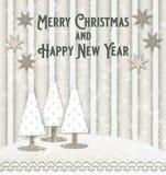 Hälsningkort för jul och för nytt år med trädjulgranar i ett snöig landskap arkivfoto