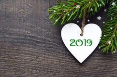 Hälsningkort för nytt år 2019 Dekorativ vit trähjärta och granträdfilial på gammal träbakgrund med kopieringsutrymme royaltyfri fotografi
