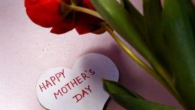 Hälsningkort i formen av en hjärta med lyckliga moders för ord dag, röda tulpan med tacksamhet arkivfilmer