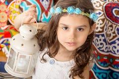 Hälsningkort: Lycklig ung muslimsk flicka som spelar med lyktan in royaltyfri bild