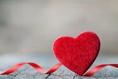 Hälsningkort på Sankt valentindag med röd hjärta för par på trätappningbakgrund arkivfoton