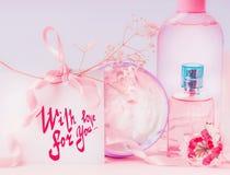Hälsningkort som läggas med textbokstäver med förälskelse för dig och rosa kosmetiskt produktatt ställa in Inbjudan, kupong, raba arkivbilder