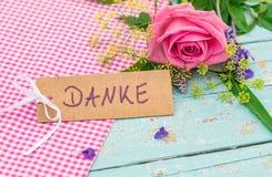 Hälsningkortet med det tyska ordet, Danke, hjälpmedel tackar dig med rosa färgrosblomman Arkivbild