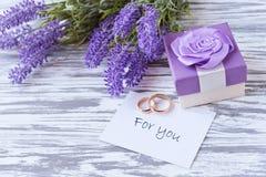 Hälsningkortet med lilan blommar lavendel med gåvaasken med tra Arkivbild