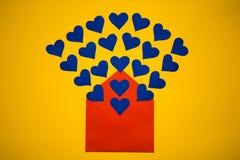 Hälsningkuvert med pappers- hjärtor på gul bakgrund Hjärtor häller ut ur kuvertet Hjärtor flyger ut från kuvertet Förälskelse Royaltyfri Fotografi