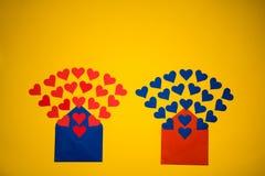 Hälsningkuvert med pappers- hjärtor på gul bakgrund Hjärtor häller ut ur kuvertet Hjärtor flyger ut från kuvertet Förälskelse Royaltyfria Foton
