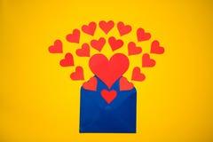 Hälsningkuvert med pappers- hjärtor på gul bakgrund Hjärtor häller ut ur kuvertet Hjärtor flyger ut från kuvertet Förälskelse Royaltyfri Bild