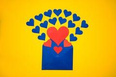 Hälsningkuvert med pappers- hjärtor på gul bakgrund Hjärtor häller ut ur kuvertet Hjärtor flyger ut från kuvertet Förälskelse Arkivfoton