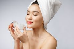 Hälso- och skönhetbegrepp - attraktiv asiatisk kvinna som applicerar kräm på hennes hud som isoleras på vit arkivbilder