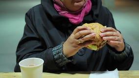 Hälsoproblem som äter för mycket Kvinna som äter den fettiga hamburgaren på snabbmatrestaurangen lager videofilmer