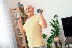 Hälsovård för övning för hög man hemmastadd med starka hantlar Arkivfoto