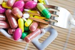 Hälsovård och wellness - banta preventivpillerar och lossavikt - olika minnestavlor i en kruka med gafflar Arkivbilder