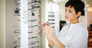 Hälsovård, synförmåga och visionbegrepp - lycklig kvinna som väljer exponeringsglas på optiklagret royaltyfri fotografi