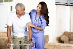 Hälsovårdarbetare och åldringman Arkivbild