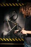 Hält Berufsreinigung eines Fahrrades in der Werkstatt instand Ein junger kaukasischer stilvoller Mann mit dem langen gelockten Ha stockbilder