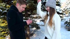 Hält einen Handy in seinen Händen und beachtet nicht das Mädchen, das ihn mit einem Ballon in Form eines Herzens schlägt E stock footage