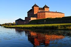 Häme castle by the lake. Häme castle is a big medieval building in Hämeenlinna Finland. Here it stands against the sky on a sunny evening Stock Image