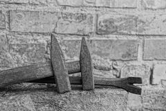Hämmer und Nägel nahe einer Backsteinmauer Lizenzfreies Stockfoto