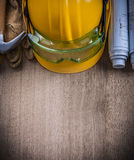 Hämmern Sie Schutzhandschuhschutzhelm der Schutzbrillenpläne auf hölzernem b Stockfoto