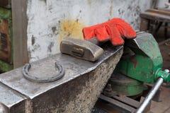 Hämmern Sie und ein Hufeisen und ein Handschuh im ironsmith Stockbild