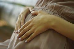 Händchenhalten der schwangeren Frau in einem Herzen auf seinem Bauch draußen stockfoto