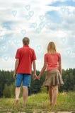 Händchenhalten des glücklichen Paars Stockfotografie