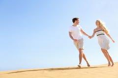 Händchenhalten des glücklichen Paars, das Spaß habend läuft Stockbild