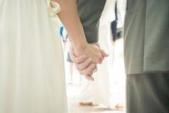 Händchenhalten des glücklichen Paars an ihrem Hochzeitstag Stockfotografie