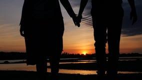 Händchenhalten eines liebevolles Paares, das bei Sonnenuntergang durch den Fluss geht HD, 1920x1080 Langsame Bewegung stock footage