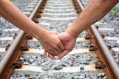 Händchenhalten eines Paares, das entlang das Bahngleis geht Lizenzfreies Stockbild