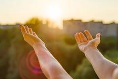 Hände öffnen sich zum Sonnenuntergang, zur Meditation, zum Hintergrund des offenen Fensters im Haus, zum Schattenbild der Stadt u Lizenzfreies Stockfoto