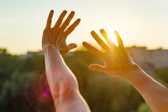 Hände öffnen sich zum Sonnenuntergang, zur Meditation, zum Hintergrund des offenen Fensters im Haus, zum Schattenbild der Stadt u Stockfotografie