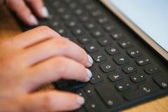 Hände auf der Tablettentastatur mit deutschen Buchstaben Das Konzept der Fernarbeit, des Freiberuflich tätig seins, blogging, des Stockbilder