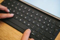 Hände auf der Tablettentastatur mit deutschen Buchstaben Das Konzept der Fernarbeit, des Freiberuflich tätig seins, blogging, des Lizenzfreie Stockfotografie