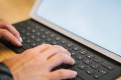 Hände auf der Tablettentastatur mit deutschen Buchstaben Das Konzept der Fernarbeit, des Freiberuflich tätig seins, blogging, des Lizenzfreies Stockbild