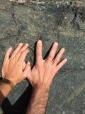 Hände auf einem Vulkanfelsen stockbild