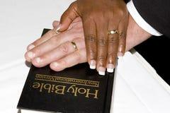 Hände auf einer Bibel Stockfotos
