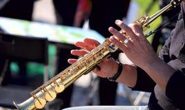 Hände auf einer goldenen Flöte Musikalisches Konzept Stra?enmusiker lizenzfreies stockbild