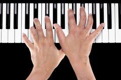 Hände auf einer Klavier-Tastatur Lizenzfreie Stockfotos