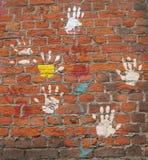 Hände auf einer Wand. Stockbild