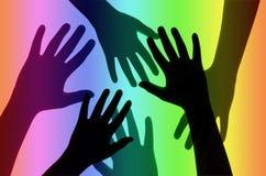 Hände auf Regenbogen-Hintergrund Lizenzfreie Stockfotos