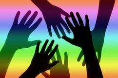 Hände auf Regenbogen-Hintergrund Stockfotos