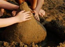 Hände auf Sandschloß Stockfoto