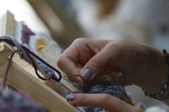Hände auf vertikaler Tapisserienahaufnahme mit beige Faden stockfotos