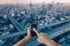 Hände bemannen das Halten von Smartphone und von blauer Stadt mit wifi Netz Stockfotografie